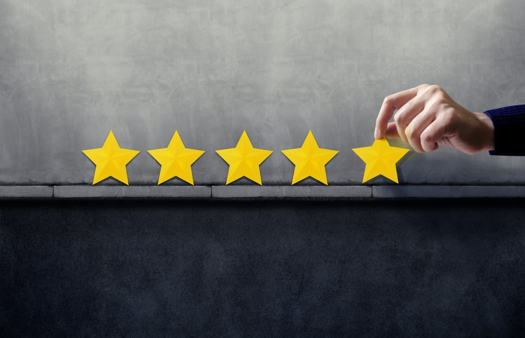 Five gold stars on a grey background. On the far right, a hand is touching the top of the last gold star, as if placing it there.